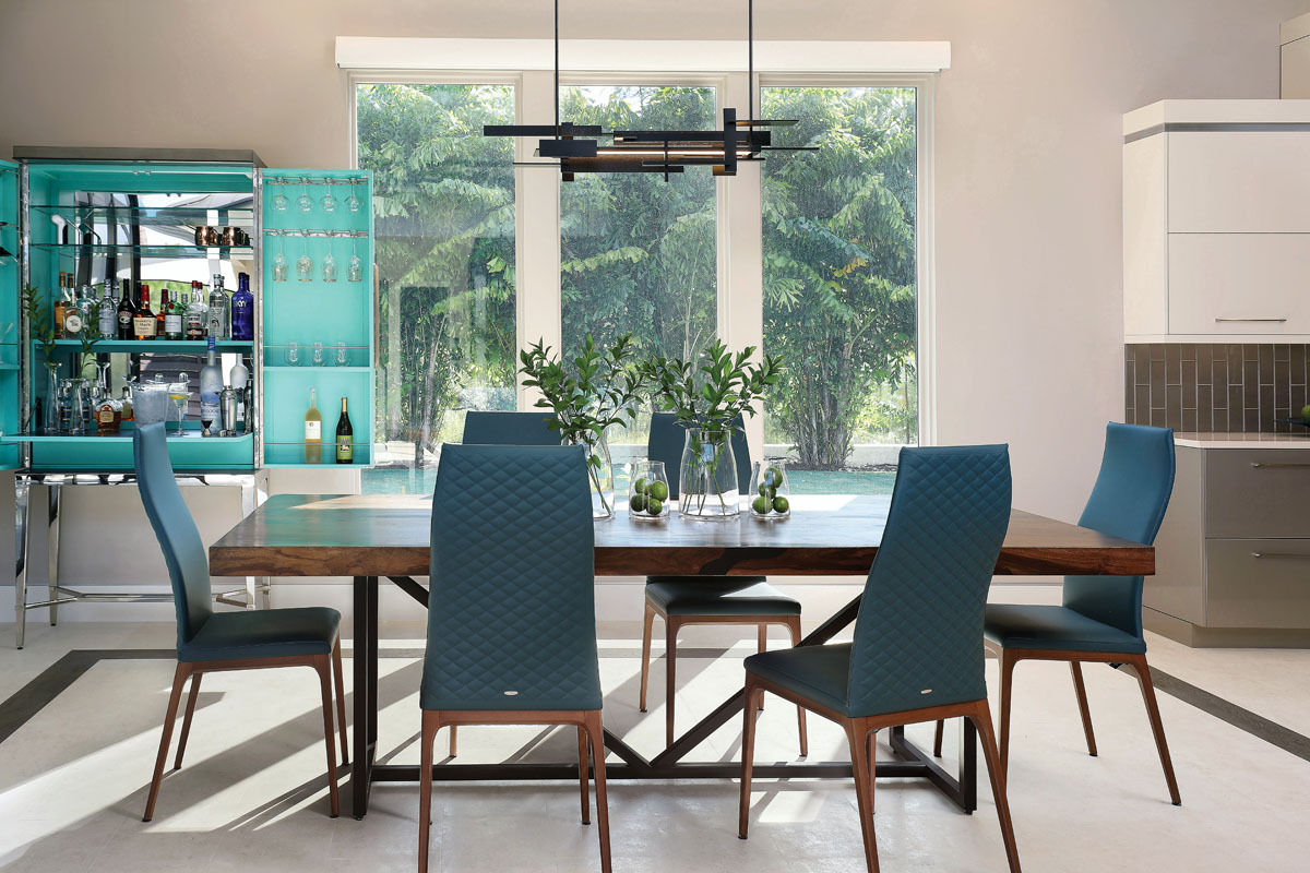 Davenport pulled blues from the kitchen island's countertop into the upholstery on the dining room chairs, and the portable bar. A walnut table and chair bases brings warmth to the room, which has a gorgeous view of the outside.