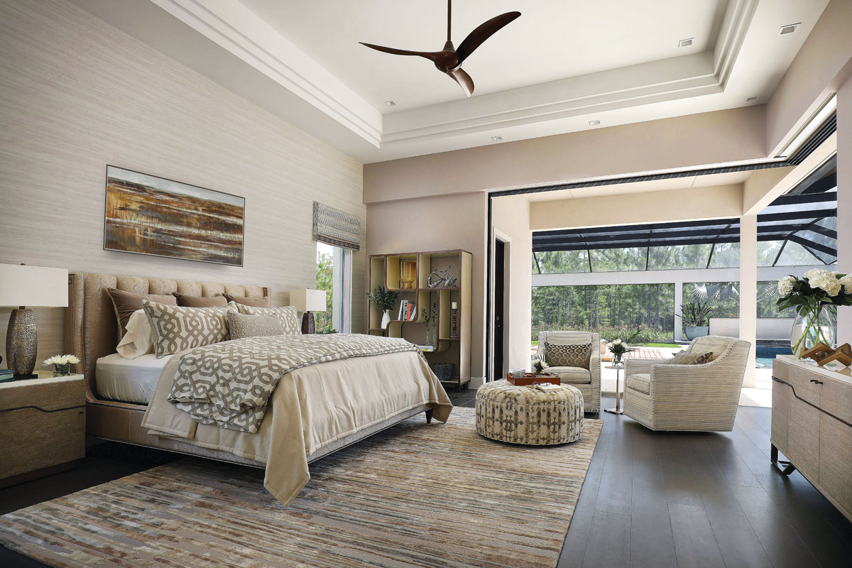 Overstuffed pillows, comfortable patterned linens, an upholstered headboard and plush chairs provide a welcome retreat at the end of a day, or a dreamlike space for breakfast in bed. Sculptural side tables and a visually arresting étagère infuse the space with crisp lines and angles. A wallpapered accent wall behind the bed offers dimension and depth.