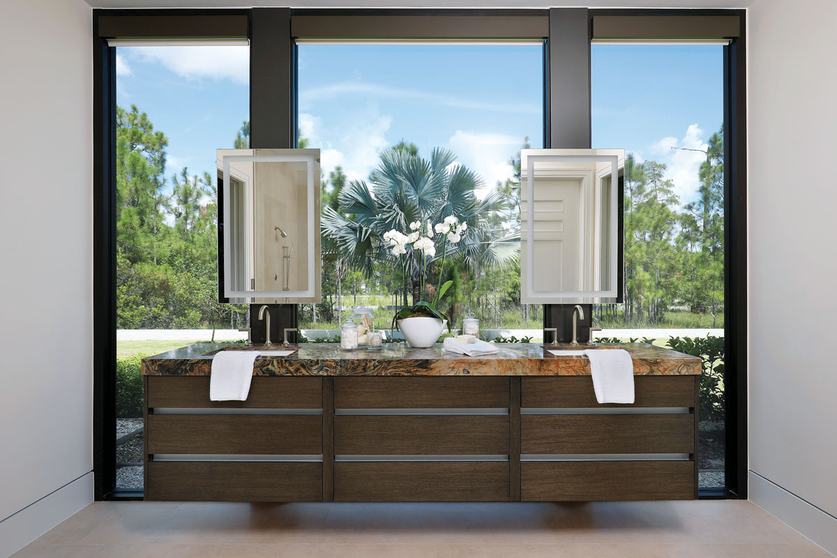 Davenport created a master bathroom with a view, by placing freestanding cabinetry featuring side-by-side sinks in front of an expanse of windows. She strategically hung mirrors so the homeowners can see both themselves and the view beyond.