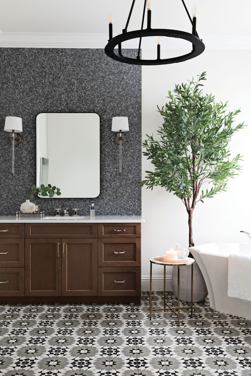 Gilmore used a stark black chandelier in the master bathroom to create a contemporary statement, and softened its severe edges with basket weave tile behind the dark wooden vanity, and a floor tile that exudes old area rug chic. A feminine, free-standing tub provides an elegant contrast.