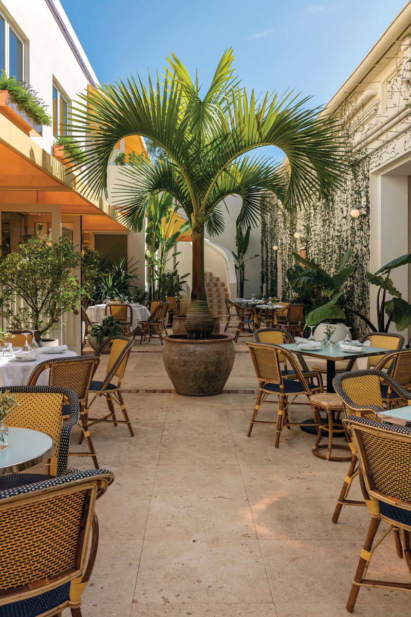 """Le Bilboquet Palm Beach features glass accordion """"nana walls"""" that open to the courtyard. The space is flanked by the curved lines of two plaster stairways, anchored by Maison Gatti rattan bistro chairs, and edged by a jasmine-laced wall."""
