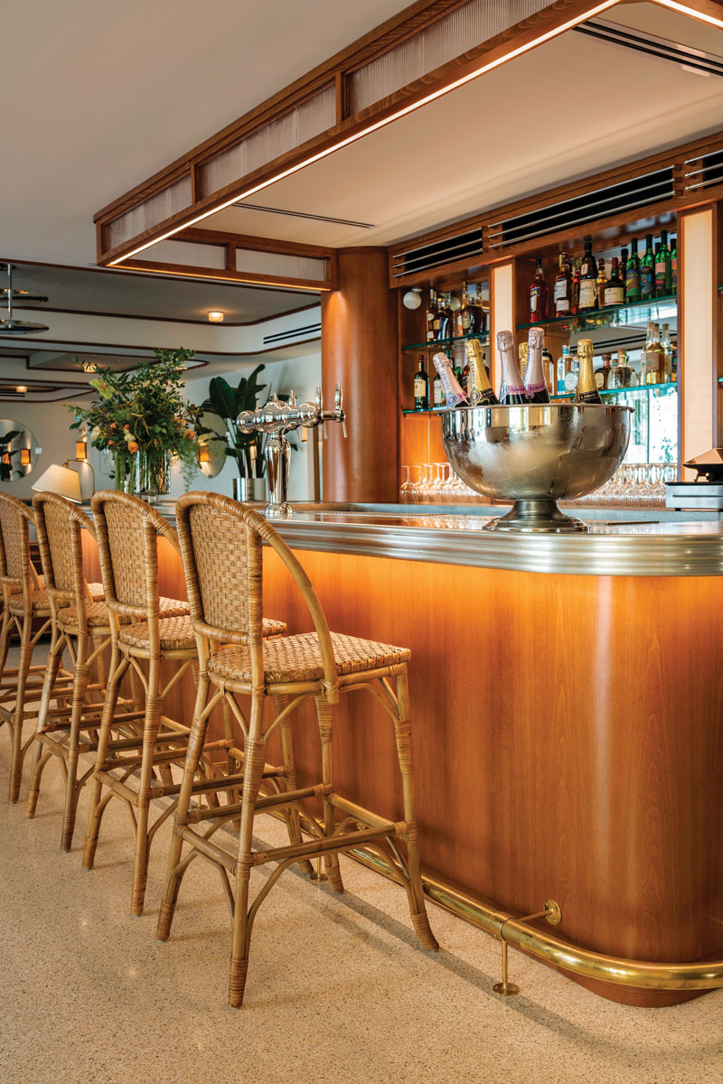 French pewter tops the Art Deco–style bar, complementing the custom cane and Jean Royere–inspired oak sconces, circular mirrors, and curvaceous furnishings.