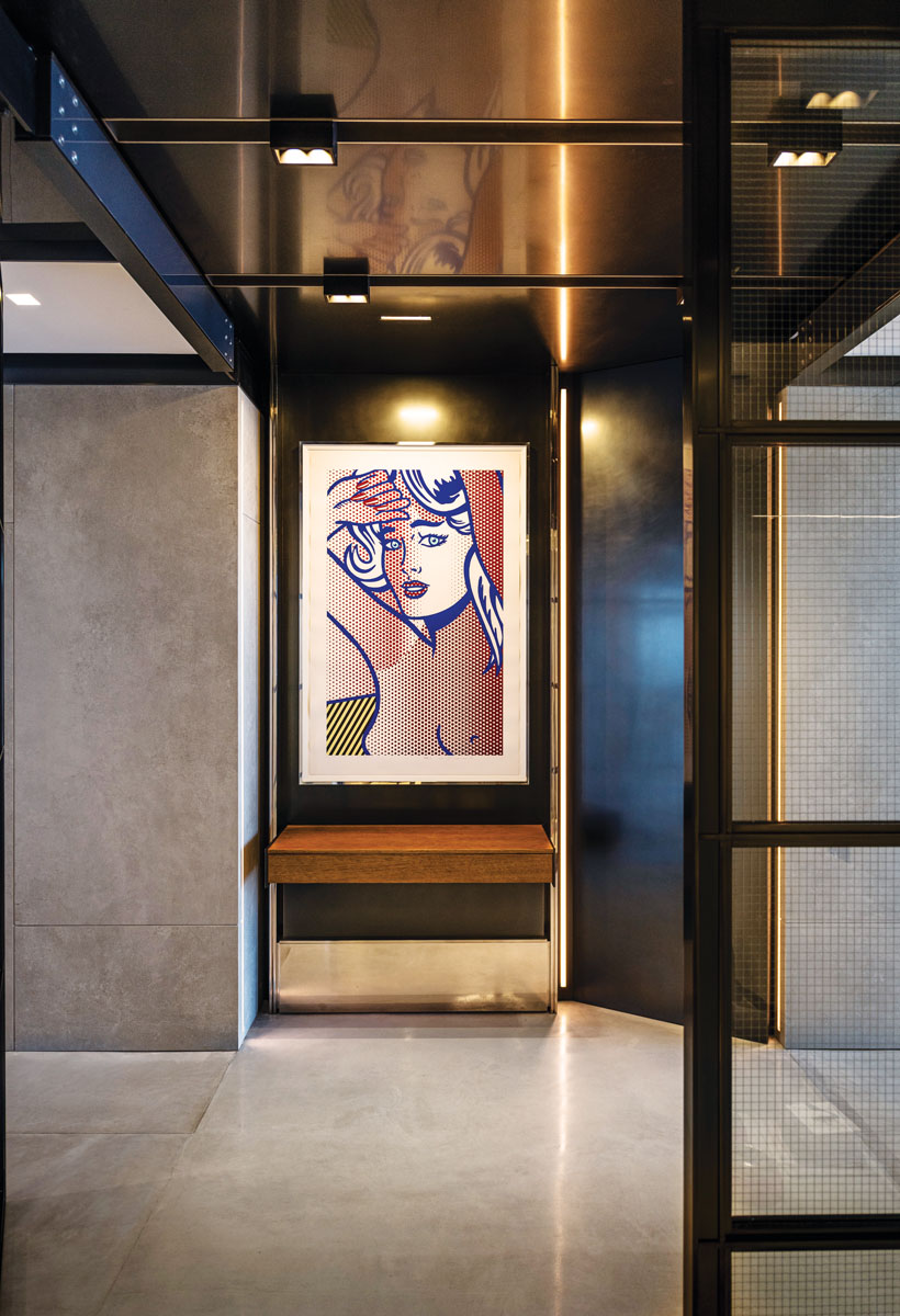 """In the foyer, the stunning """"Nude With Blue Hair"""" by Roy Lichtenstein (1994) relief print reigns supreme. The contemporary piece creates conversation and color with its strategic placement above the floor of polished concrete."""