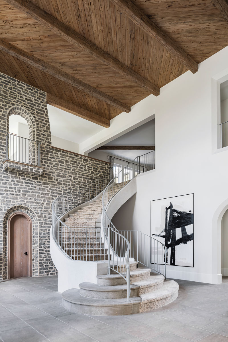 The grandeur of the stairway announces entry to the elegant country estate, where a black-and white abstract painting adds a modern complement. A patterned oriental rug by Kravet was custom-colored and installed to follow the stairs' curves. Reclaimed French pine beams span the 24-foot-high ceilings clad in whitewashed pecky cypress in a herringbone pattern.