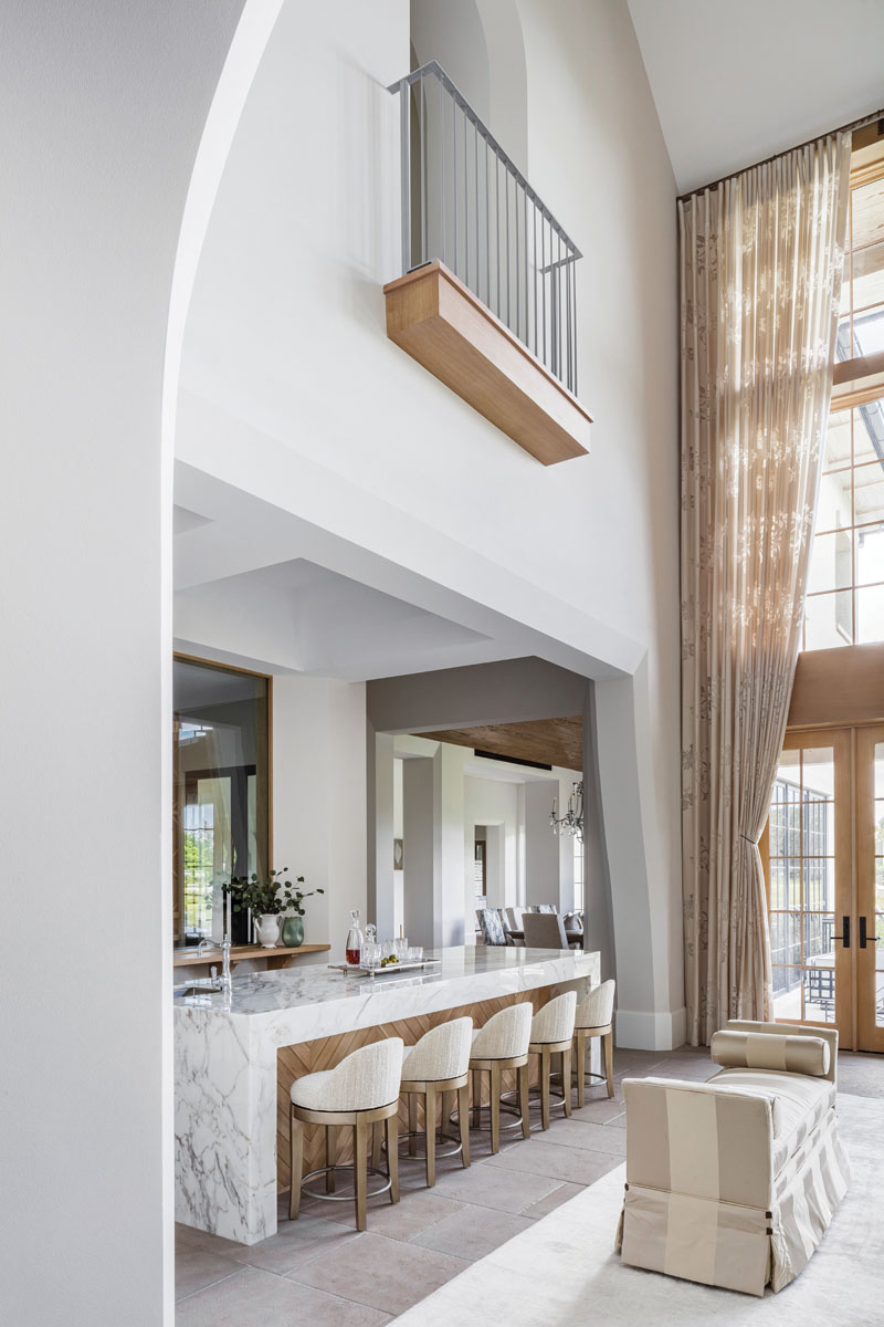 """""""All of the furnishings have very tailored lines, but rich chenille and warm solids mix with floral prints and wide stripes to pull it all together in a soft and airy look,"""" interior designer Jenny Zalkin says."""