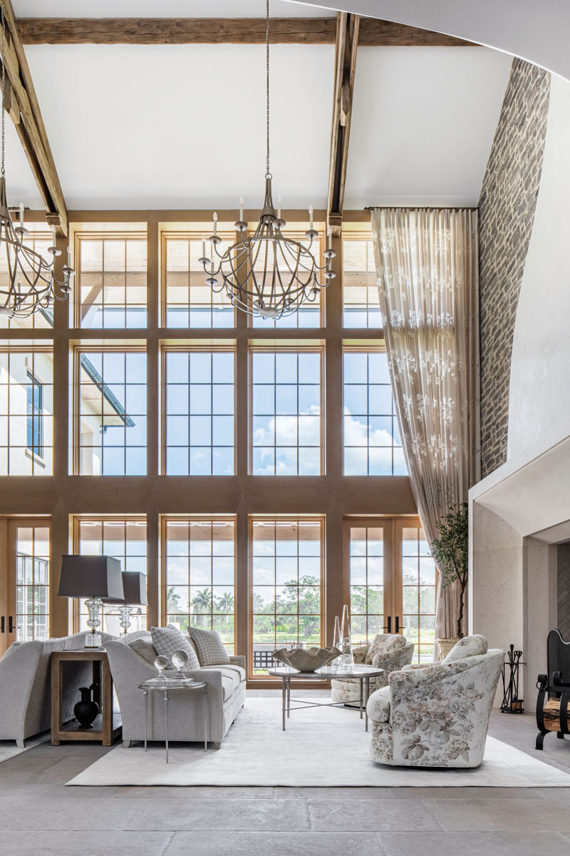 In the living room, Luciano Marcato's draperies pull open to reveal stunning floor-to-ceiling windows. Kravet's sofas pair with club chairs from Century Furniture on one side of a conversational grouping; a boldly striped settee anchors the opposite side.