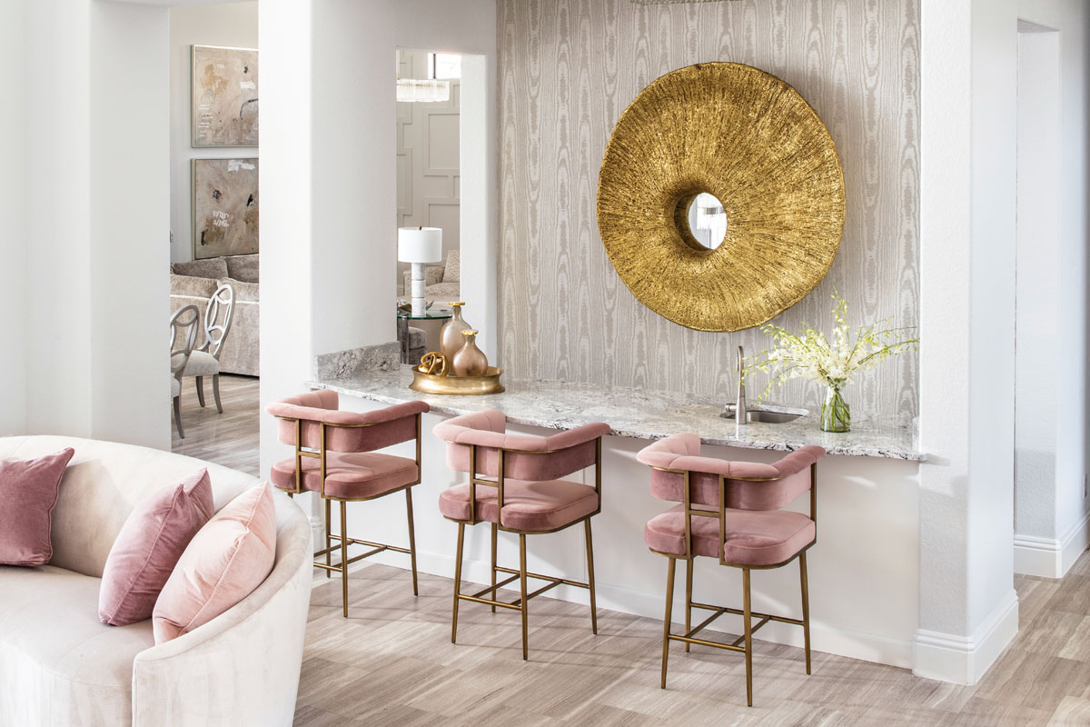 To establish a focal point in the living room bar, Kairis installed metallic faux bois wallpaper by JF Fabrics. The 5-foot diameter mirror from Phillips Collection is made of gold leaf over resin.
