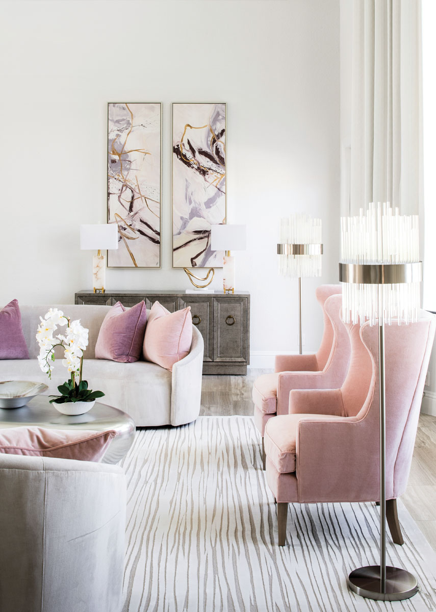 In the formal living room, custom velvet throw pillows coordinate with the CR Laine wing chairs. The coffee table is one of two in the shape of river rocks, covered in silver leaf, atop a Jaipur Living rug.