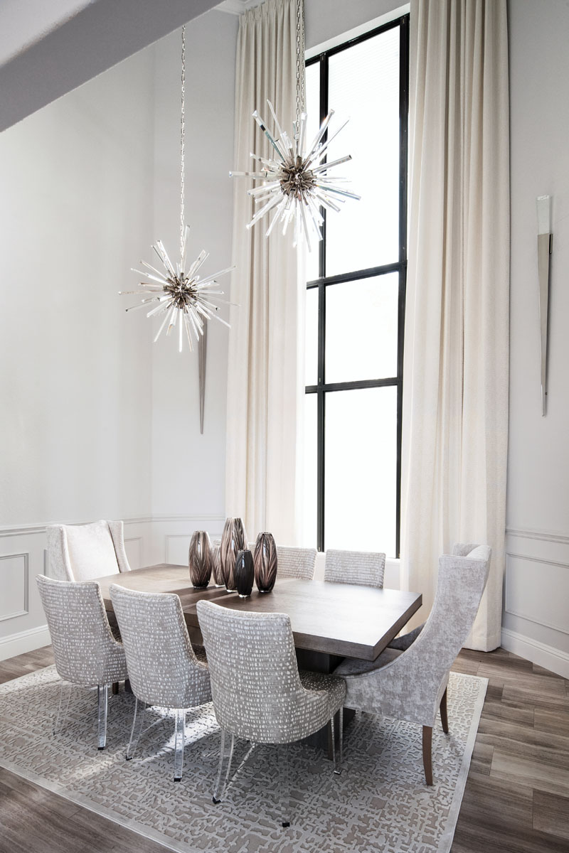 Starburst chandeliers from Arteriors, hung at different lengths from the 26-foot high ceiling, light the 8-foot dining table from Bernhardt. The wall sconces are from Modern Forms. Host chairs are from CR Laine, while the side chairs are custom.
