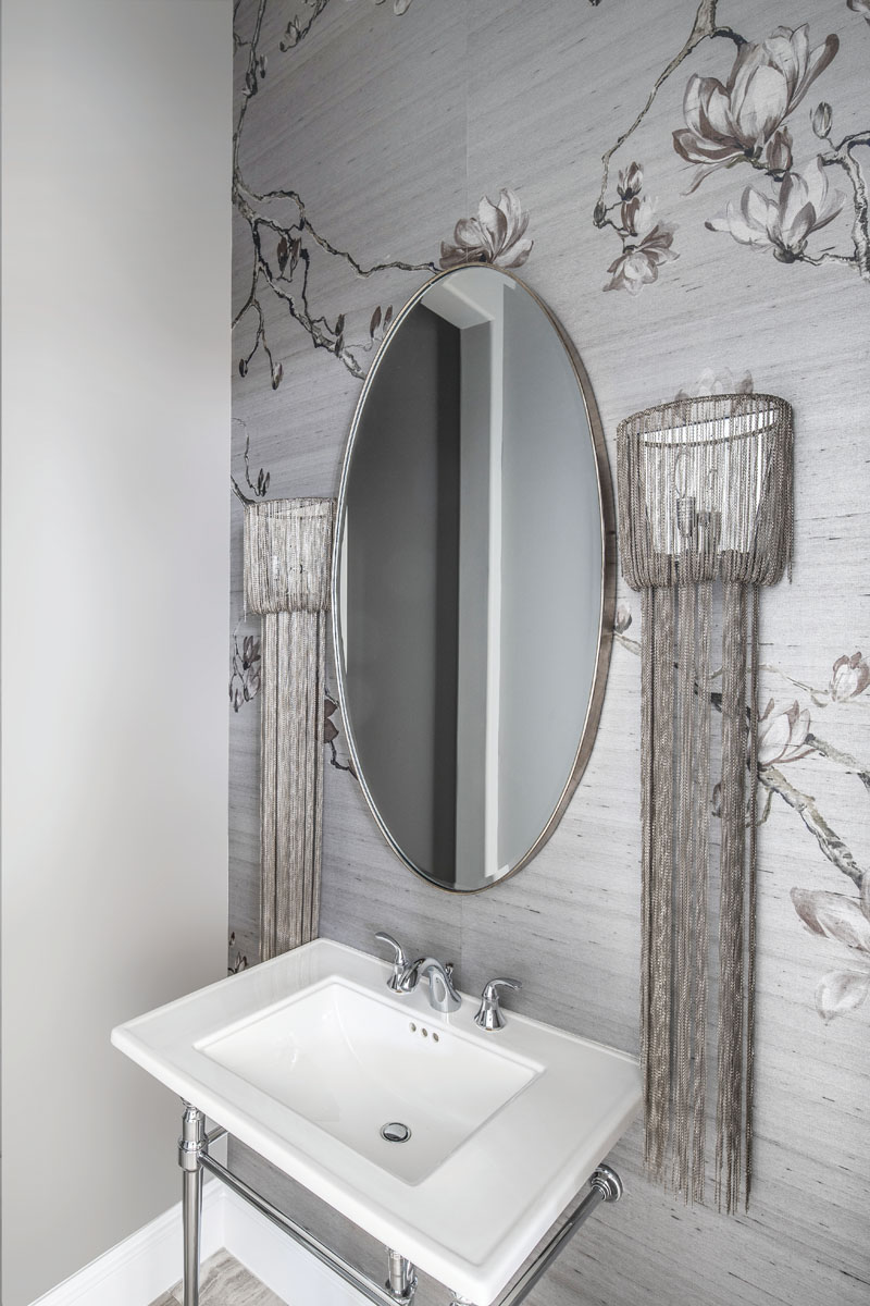 """The client wanted """"something beautiful"""" for the first-floor powder room, so Kairis installed hand-painted silver silk Blossom wallpaper from Phillip Jeffries. The antique nickel sconces by Arteriors feature 45-inch long chains."""