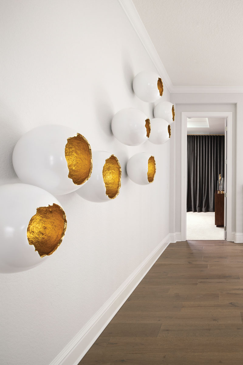 The second-floor hallway leading to the master bedroom features broken egg art from Phillips Collection. The interior of the eggs is painted with gold leaf and reflects the natural light, making them appear lit from within, says Kairis.