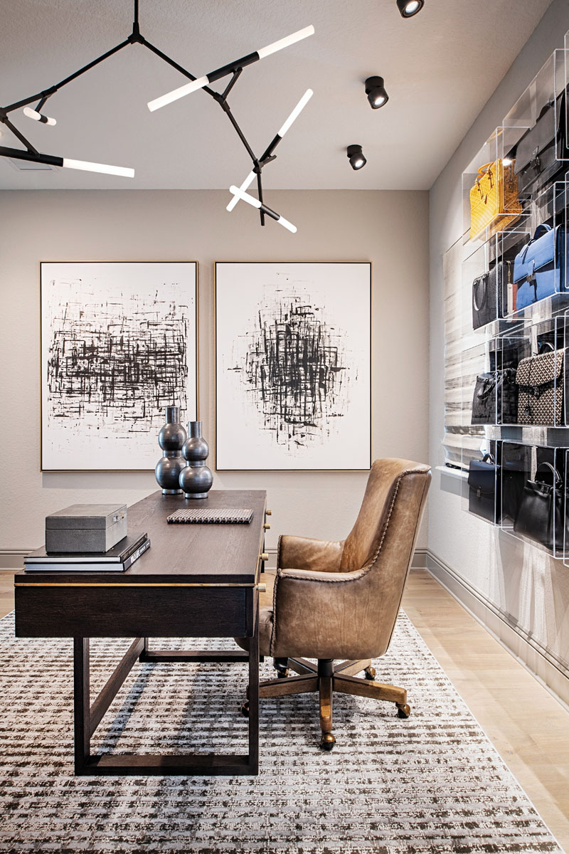 """Kairis installed custom Plexiglas display cases in the husband's office to showcase his collection of luxury briefcases. """"It was like putting together a puzzle, with the various colors and textures,"""" she says. The black and white art is by artist Giselle Kelly for Leftbank Art."""