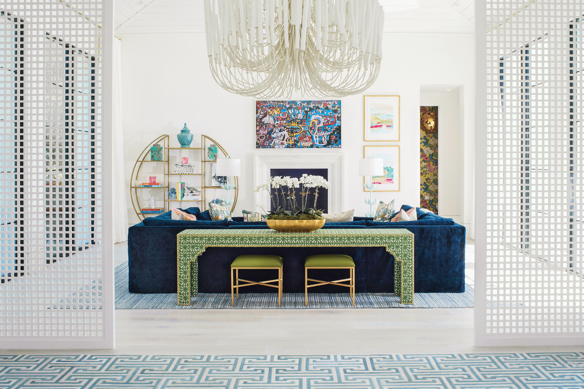 Above the fireplace, a colorful work of art transforms into flat screen TV for a now-you-see-it-now-you-don't effect. It's juxtaposed by a gold leaf spherical etagère from Regina Andrew. The white Tilda chandelier from Arteriors anchors the space between the living and dining areas.