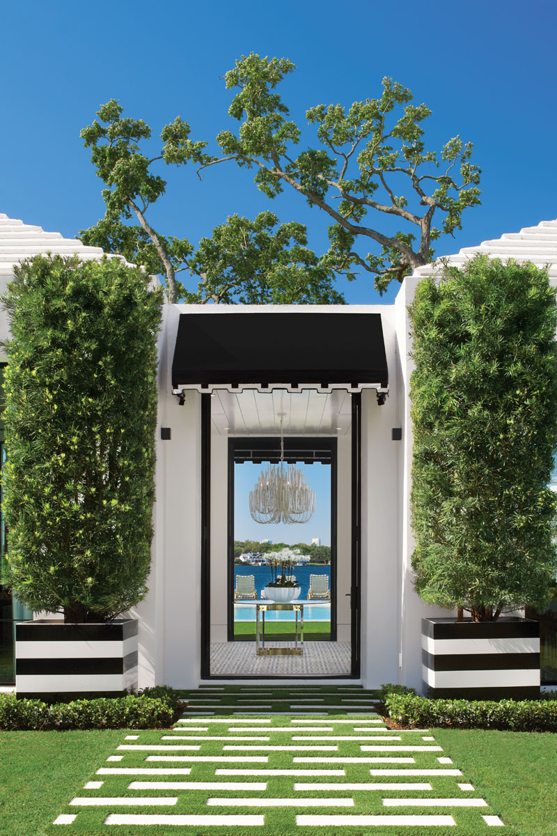"""Designed to intrigue guests, the black metal framed front door is flanked by a set of black and white striped planters and topped with a scalloped edge awning. """"One of our favorite design features in the house is the foyer,"""" say the homeowners. """"As you enter the front courtyard, it invites you into this clear nature view of the oak tree and the lake just beyond the unique circle pool."""""""