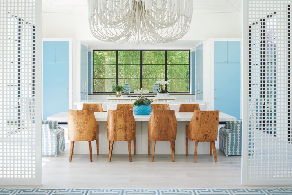 With an open floor plan, Emily and Zane wanted to differentiate each space without disturbing the flow. Here, white custom designed screen panels separate spaces. Mixing patterns becomes a work of art as whimsical turquoise and white dotted upholstered chairs play off of the Greek key rug.