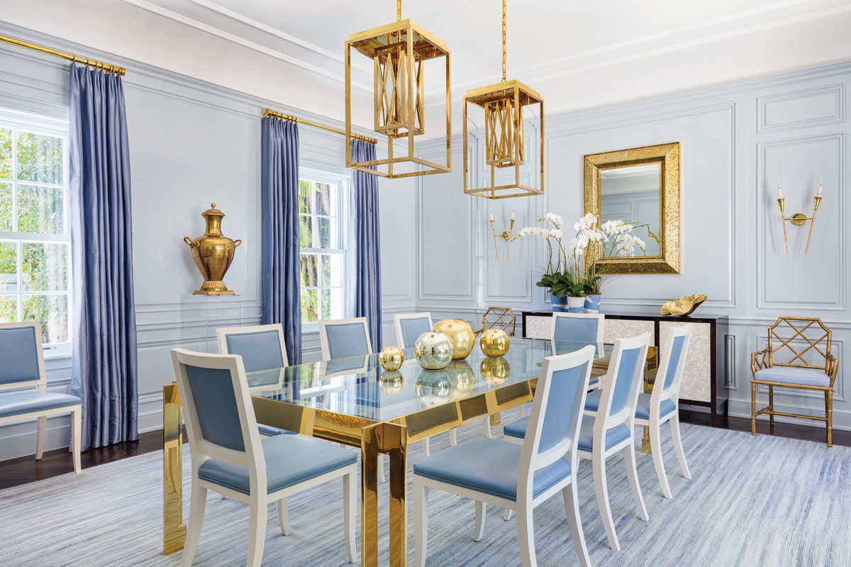 """Interior designer Scott Sanders used seventeen layers of pale blue lacquer to give the dining room's paneled walls a fresh, modern look. In the middle of the room, he placed a large brass and glass table, and infused the room with brass accents. The McLean Wiesand dining room chairs are an obvious nod to Palm Beach, Sanders said, """"but in a cleaner way with the white and the leather."""""""