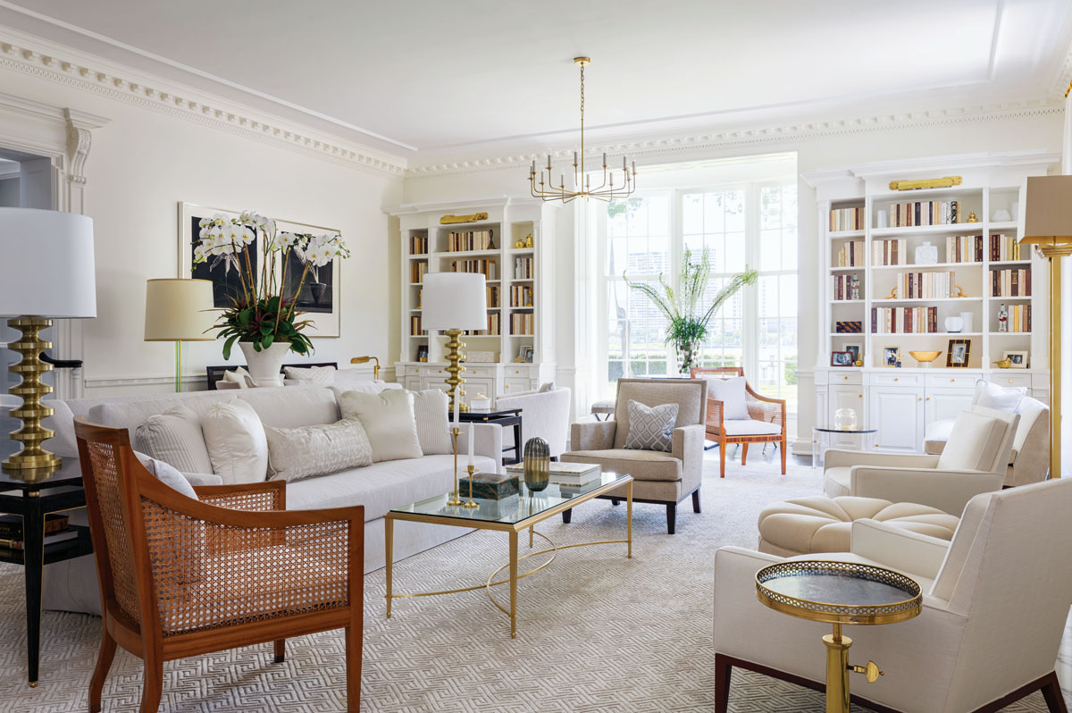 """Smith, project manager Angie Lehman, and interior architect Angelo Davila teamed up to restore the sunken living room's original trim and added built-in corner bookshelves. Sanders created a creamy-hued, classic, and comfortable room filled with a mixture of vintage and modern pieces. """"We didn't want it to be one of those rooms you roped off and used for the holidays,"""" he said."""