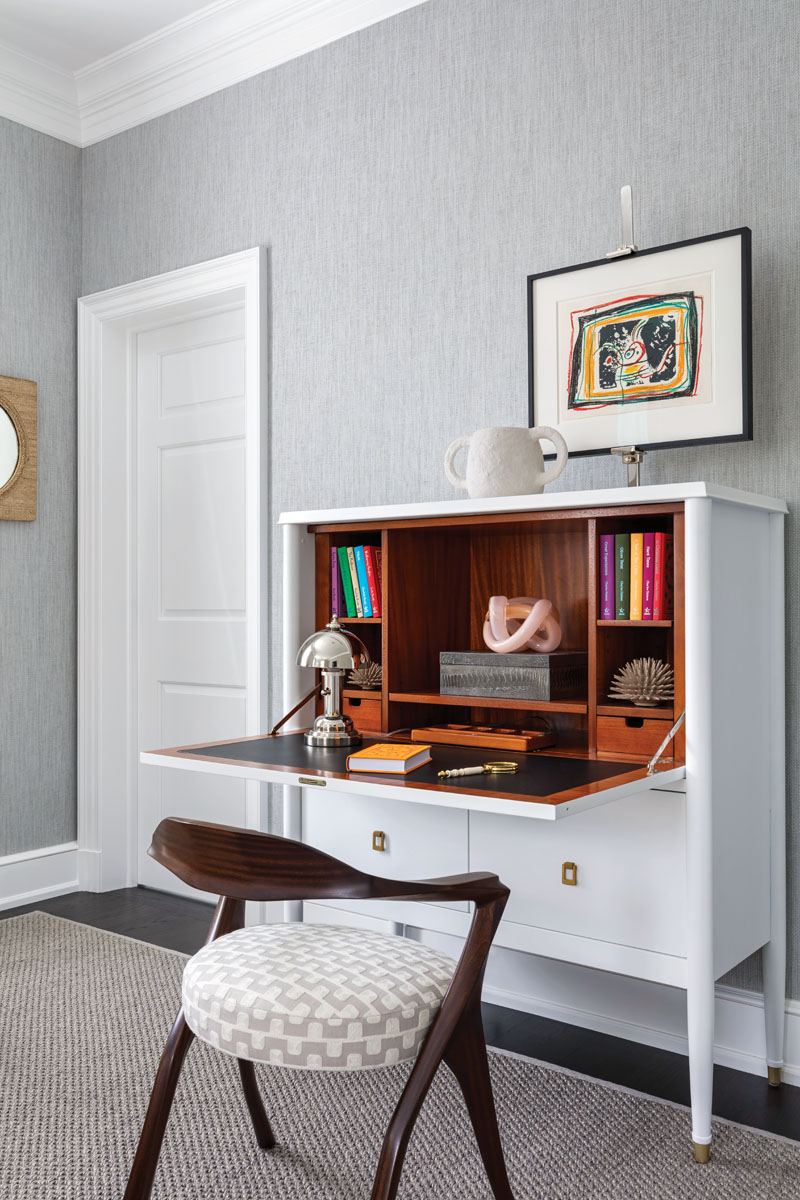 """In a guest room, Sanders created an inviting space with a relacquered, upright desk, a sleek antique chair, and a framed Joan Miro lithograph. """"It's a special moment, a sweet vignette,"""" he said. """"When you see it, you want to sit there."""""""