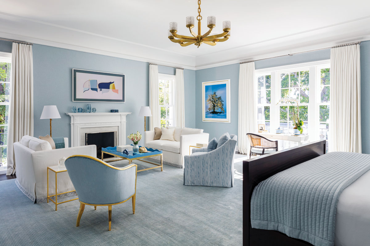 """For Sanders, this sun-kissed room was """"a very challenging space"""" because it was so large and square. To make the soothing pale blue room feel more intimate, he subdivided it into three areas: one for sleeping, another for writing letters, and a third for sitting around the fire and watching television."""