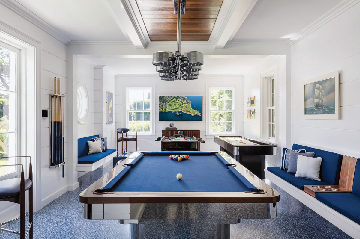 The homeowner likes nautical style, so Sanders went in that direction in the game room—covering the walls in shiplap and maritime art, creating custom banquettes with drink holders, and hanging a vintage boating-inspired nickel lighting fixture over the pool table.