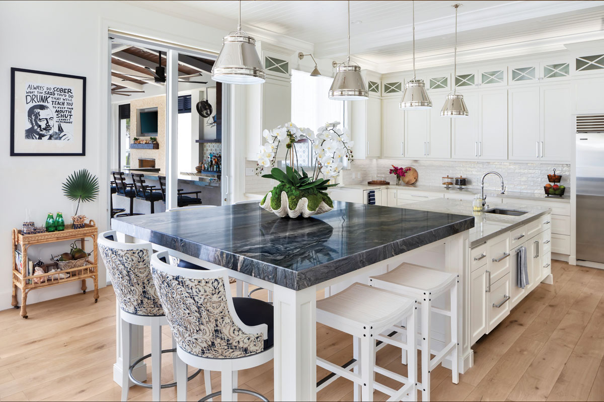 The kitchen island featuring a three-inch countertop in Calico Blue quartzite matches the cabinetry and is connected to the lower part of the island. Fabric barstools from Century Furniture bring in texture, while the four Currey & Company light pendants capture a nautical feel.