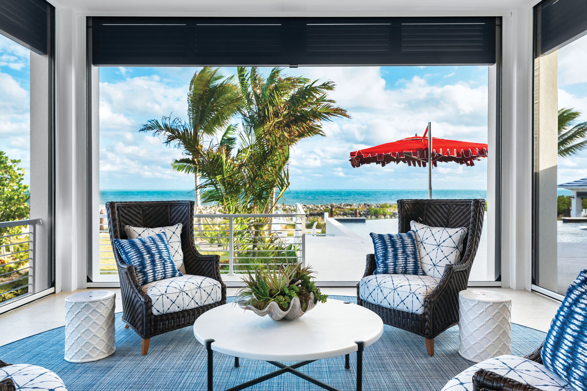 Every ocean-facing outdoor space is enclosed with automated roll-down hurricane shutters and a screen layer. This space features chairs and a cocktail table by Tommy Bahama for Lexington, garden stools by Surya, and a rug by Fibreworks.