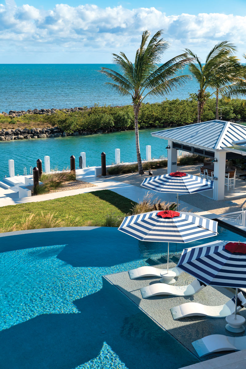 """""""We wanted an outdoor living space that was the focus of our home—literally we wanted a house attached to a pool area,"""" says the client. With unobstructed ocean views, this space is loaded for entertainment with an outdoor kitchen, a gazebo, and an infinity pool lined with lounge chairs. Inspired by Ralph Lauren's classic blue and red Americana vibes—a client favorite—the umbrellas are by Tuuci."""