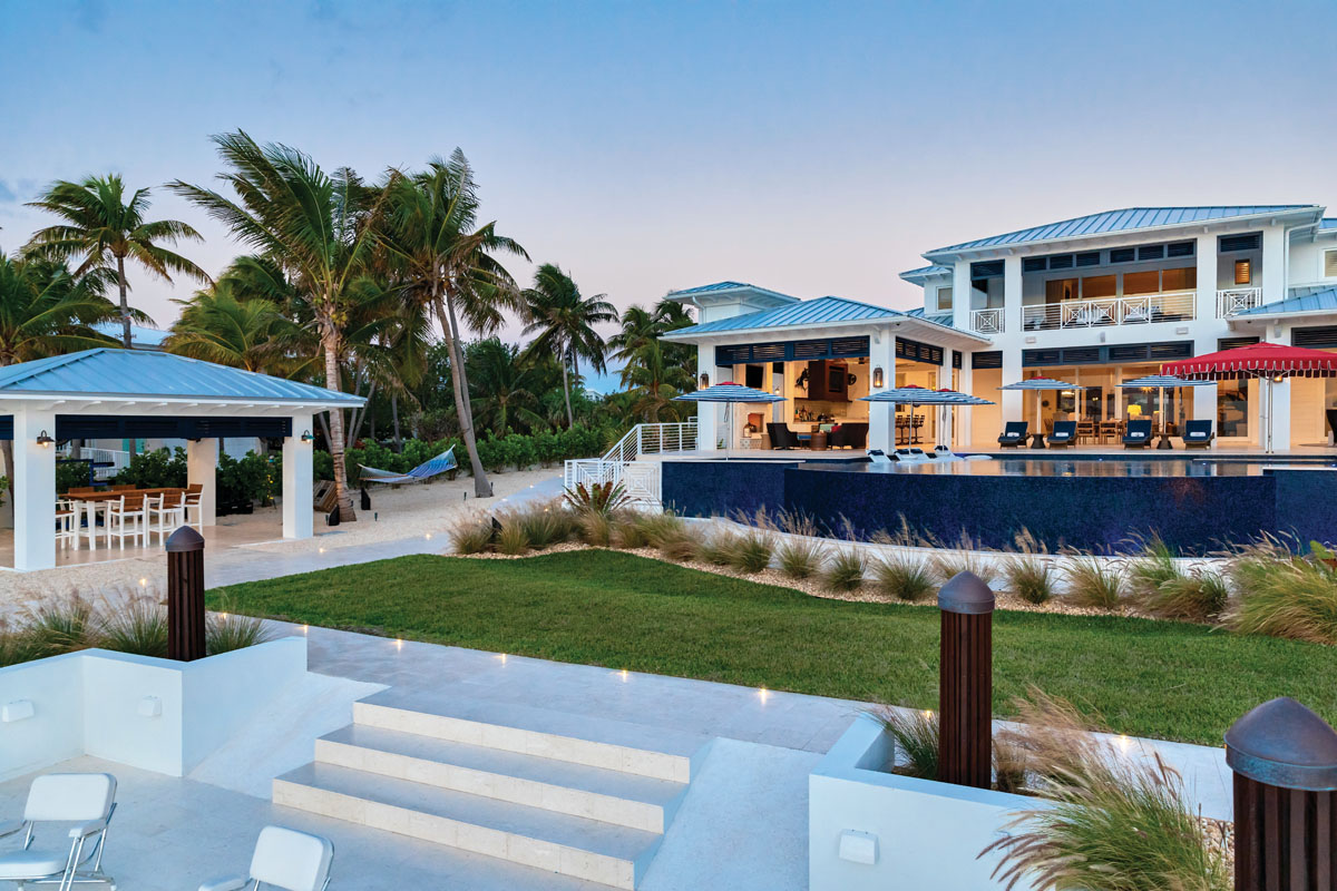 Designed to feel like an extension of the ocean, the pool features a large spillover wall in navy glass tile by Mosaicist. An in-pool swim up bar seating is a prime spot to watch the boats go by. Under the gazebo is a marine-grade, polymer, bar-height table for rigging fishing lures.