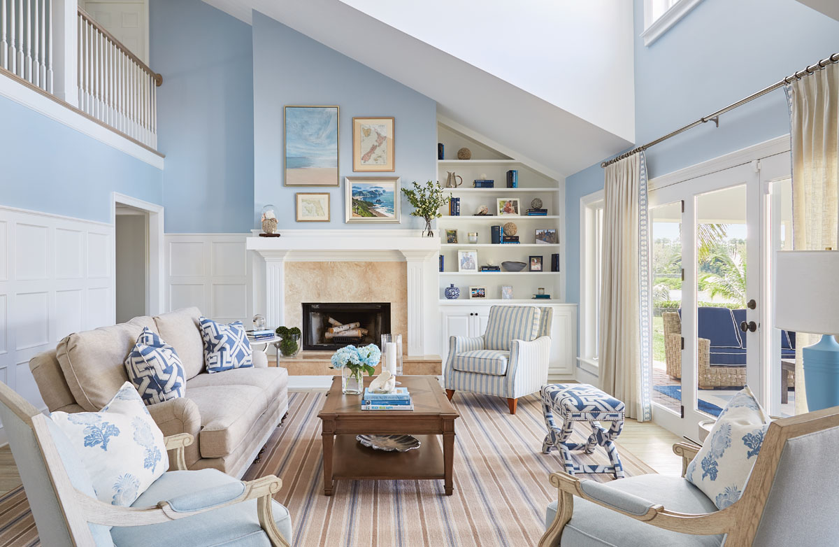 """In the living room, a mix of blue hues and sandy tones feels serene while patterns and geometrics keep the design dynamic. Vanguard's sofa and armchairs shape a seating area. Libby Langdon's own striped """"Halsey"""" for Fairfield offers the comfort and ease of a recliner with the styling of a chic lounge chair. Libby Langdon Vero 31-2APhotography by Aric Attas, Creative"""