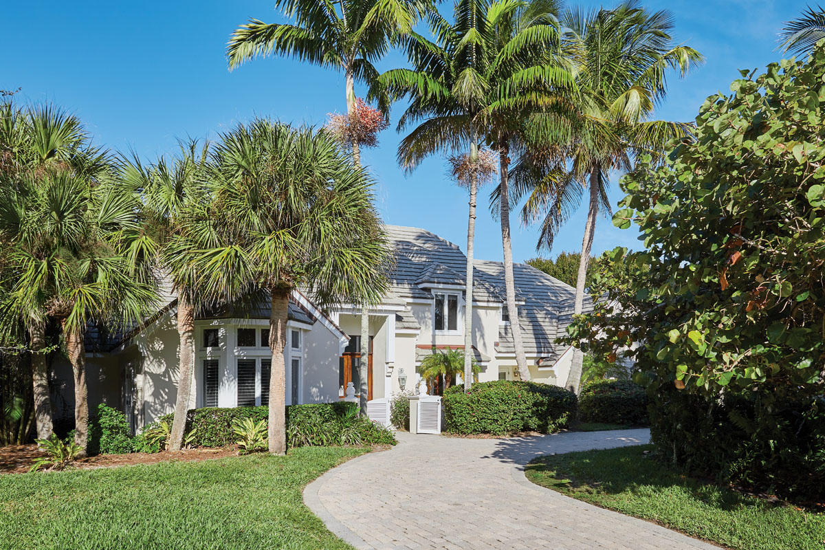 """""""We lightened and brightened the exterior with Benjamin Moore's 'Sail Cloth,' a crisp and clean, soft sandy hue that lets the white trim shine,"""" interior designer Libby Langdon says. Libby Langdon Vero 31-2BPhotography by Aric Attas, Creative"""