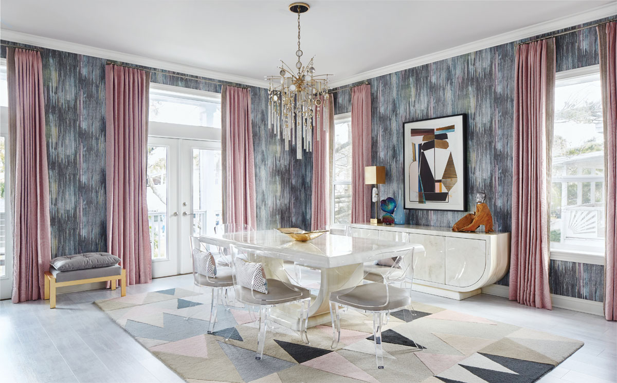 Robyn Branch_FD31-2A Photography by Zeke Ruelas Photography, Nashville, TN Designer Robyn Branch hung a dramatic, jewelry-like chandelier over the sleek white dining room table that once belonged to the client's mother. Pink draperies, pink-and-gray patterned wallpaper, and Lucite chairs provide youthful sophistication to the room. The triangle-printed rug has the added bonus of being dog friendly.