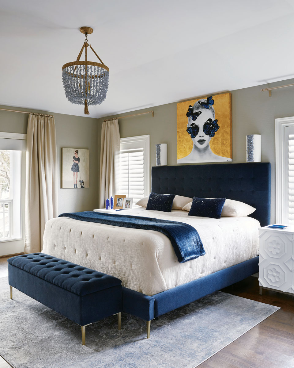 """Robyn Branch_FD31-2E Photography by Zeke Ruelas Photography, Nashville, TN In the master bedroom, Branch hung """"girly"""" artwork, thick metallic thread draperies, and a chandelier to create a soothing retreat with a few glittery flourishes. Navy blues and whites offer a grownup touch, while the bench at the foot of the bed helps the client's dogs reach the bed."""
