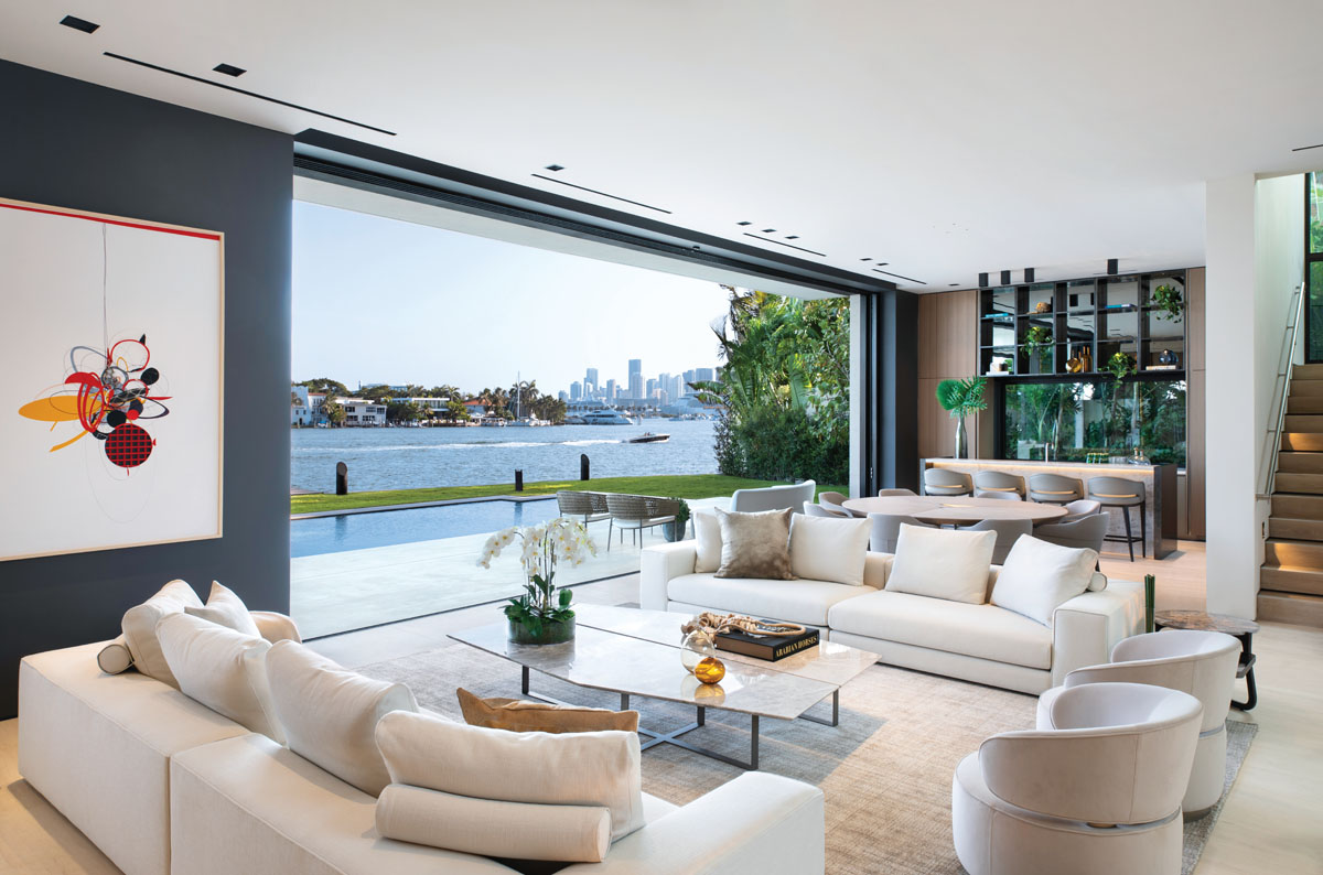 Blending the indoors with the outdoors, this chic open plan embodies the ideal combination of modern architectural simplicity and unobstructed Miami skyline views. Apure track lighting delineates the space above Artefacto's Maddox sofas and Carrie lounge chairs.