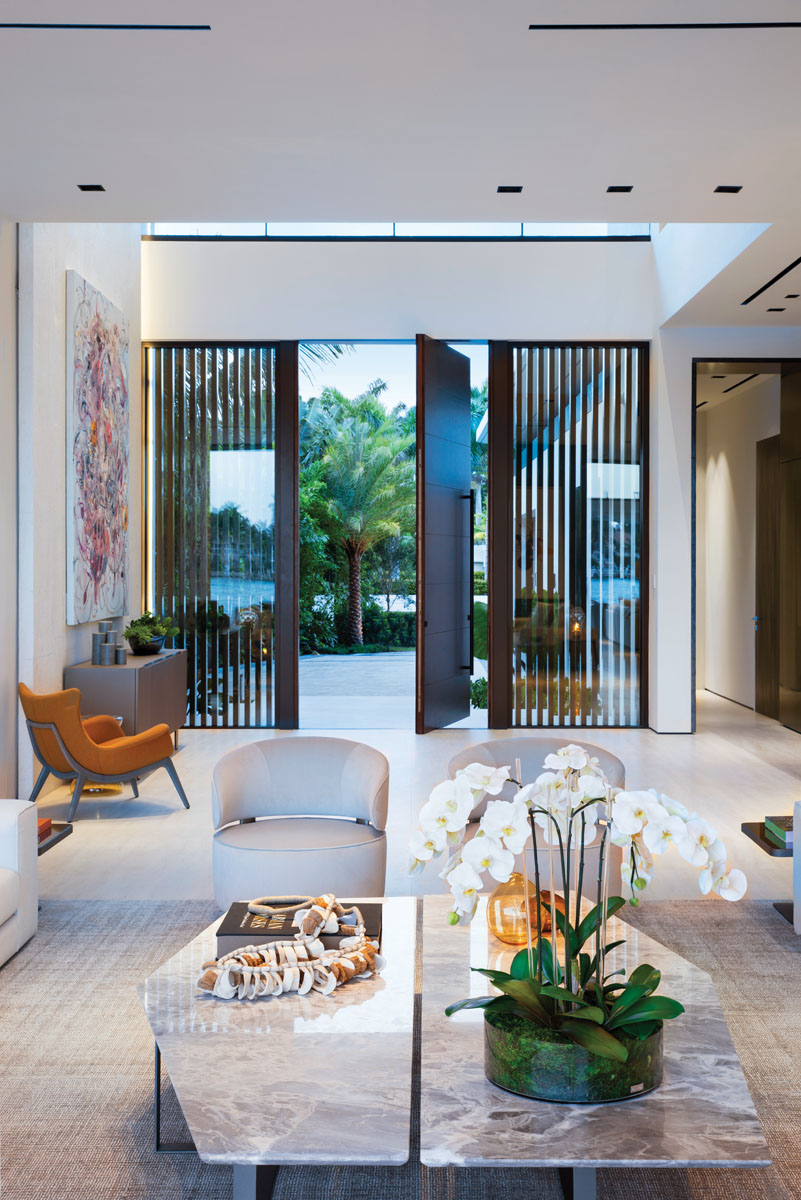 Stucco and coral stone styles the home's exterior front entry, where floor-to-ceiling windows frame a custom, solid-wood door from Honduras that pivots open to welcome guests.