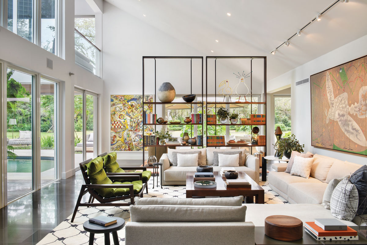 A massive metal étagère by Baxter stands up to the double height ceiling and serves as a screen that creates an intimate corner, but retains the views.
