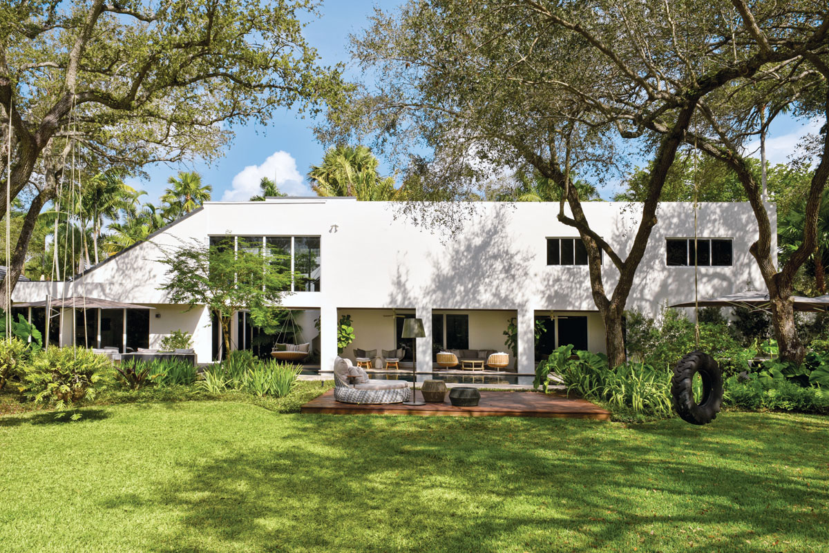 In 2017, the homeowners bought the lot behind the house to create an expansive yard. A tractor tire swing offers a playful but quaint Old Florida moment. Because the home is all angles or squares, all the outdoor pieces chosen are round, and made of synthetic wicker to survive the Miami weather. A simple but significant change was made to the back of the home's architecture, when skinny metal tube columns were expanded to almost two feet wide and squared off to provide a framed view of the pool and lawn.