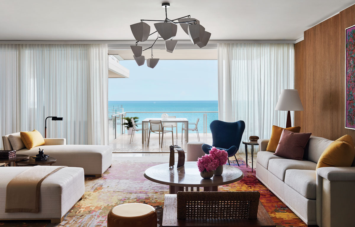 The living room's floor-to-ceiling windows open to pristine views of the Atlantic Ocean. Oak-reeded wall panels, a Fernand Dresse resin coffee table, and a custom chandelier from Andrea Claire Studio generate a warm and inviting atmosphere to offset the cool ocean blues.