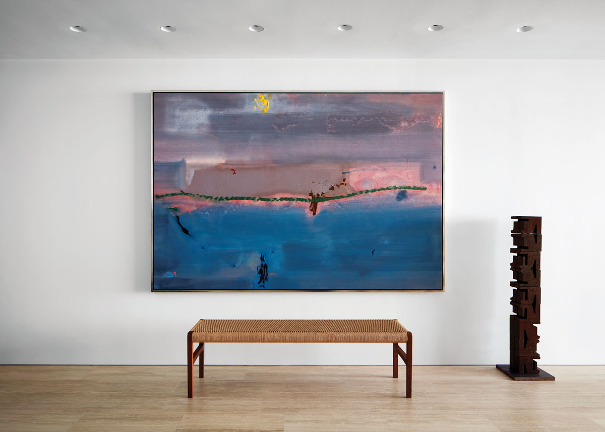 Helen Frankenthaler's By Wind and Water (1982) presides over the entry gallery in dreamy blues and mauves. Flanking the walnut corded bench is a contemporary sculpture by Marianne Vitale constructed from railroad parts.