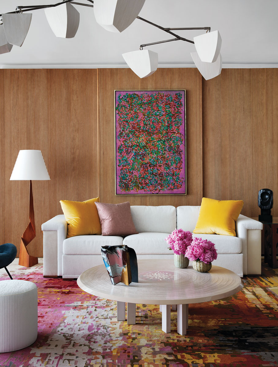 The rosy palette of an early Ad Reinhardt painting (1949) determined the rich, jeweled tones of the living room, complemented by a custom rug from Stark Carpet and gold and pink pillows in Fortuny and Schumacher fabrics.