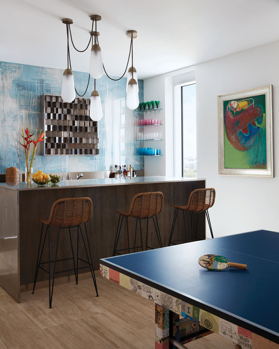The husband's passion for ping-pong inspired the lounge's playful mixed-media ping-pong table, a commission created by Tad Lauritzen Wright. Behind the bar, reverse-painted aluminum panels brighten the space and highlight the light box sculpture by Gianfranco Fini (1970) and a painting by Hans Hoffman.