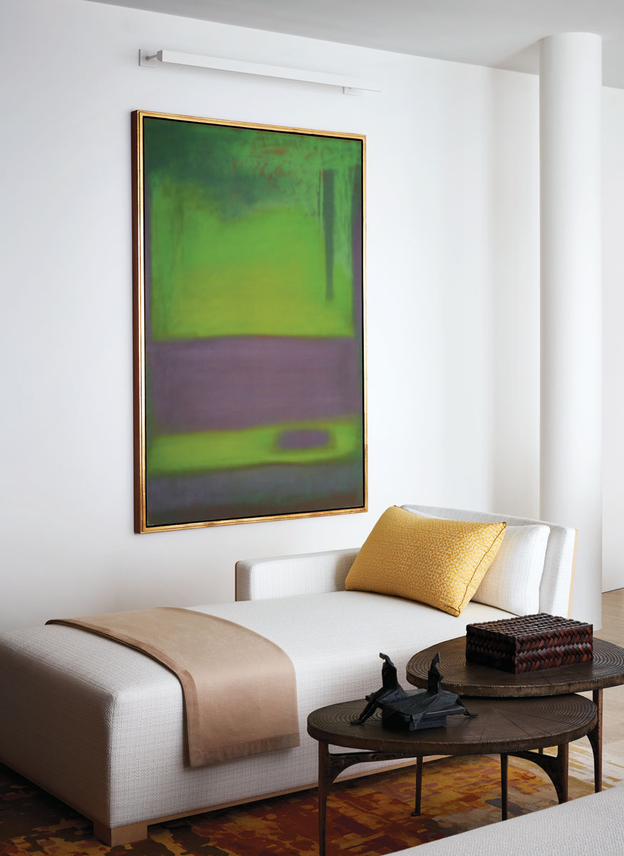 Clad in soft, resilient fabric, the luxurious living room chaise and gold Fortuny pillow sit below an Esteban Vicente painting (1976).
