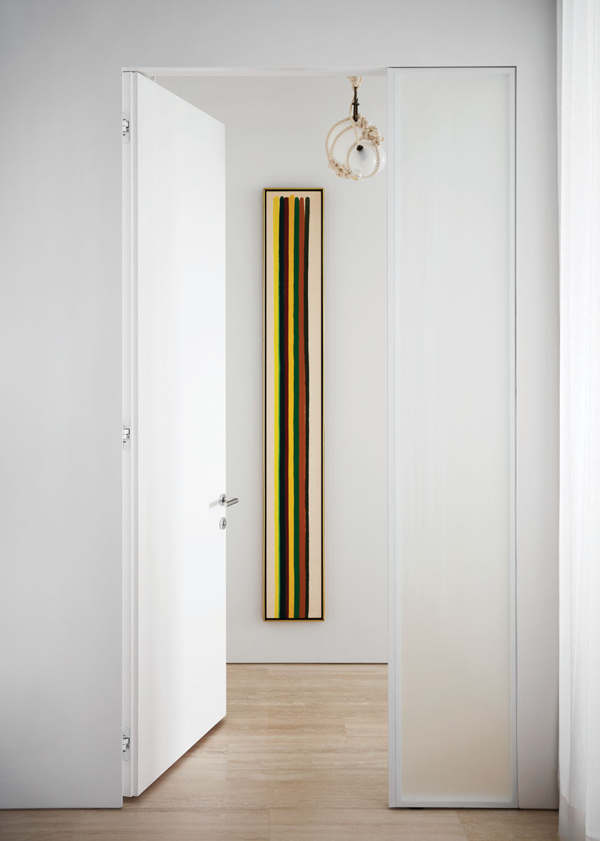 """A narrow Morris Louis painting from his 1960s """"Stripe"""" series fits perfectly in the entrance to the primary bedroom."""