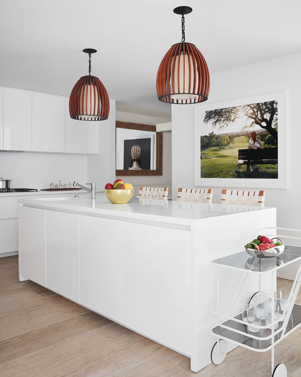 Originally an enclosed space, Scott redesigned the kitchen with a view through the dining room onto the Atlantic Ocean. White Corian countertops offset the soft greens of a large-scale photograph by Marta Soul, a tribute to the husband's love of golf.
