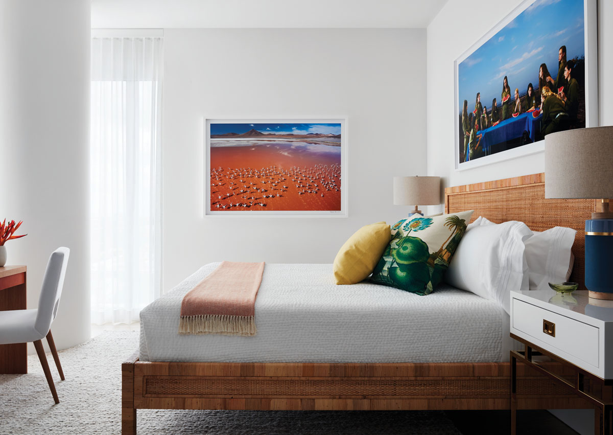 Luscious textures abound in the guest room with a hand-knotted silk and jute rug and a rattan bed. Scott balances the neutral tones with pops of vivid color from the cerulean bedside lamps, printed pillows, and two large photographs: Angelika Sher's The Watermelon Eaters (2017) and a print of a flamingo colony by George Steinmetz.