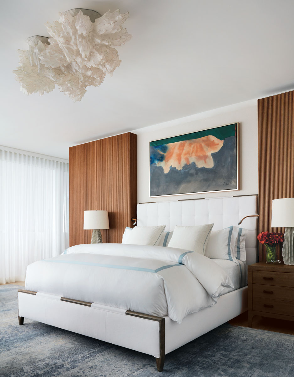 A polymer and glass light sculpture glows softly above the bed. Its cloud-like shape motivated the purchase of Helen Frankenthaler's color stain canvas, Taurus (1963). Oak-reeded wall panels match the living room and office.