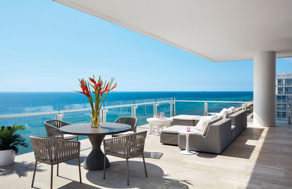 The family can take in the glorious oceanscape on a lush sectional sofa with attached chaises. A sculptural John Dickinson coffee table and hourglass concrete dining table soften the angular architectural lines.