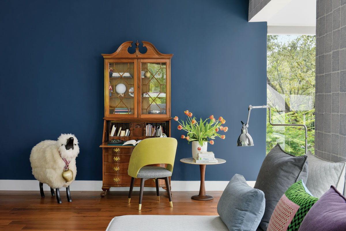 In another corner of the family room, an antique secretary desk that was a gift from the wife's aunt is effortlessly juxtaposed with modern pieces like the yellow chair from Baxter and surrounding décor.