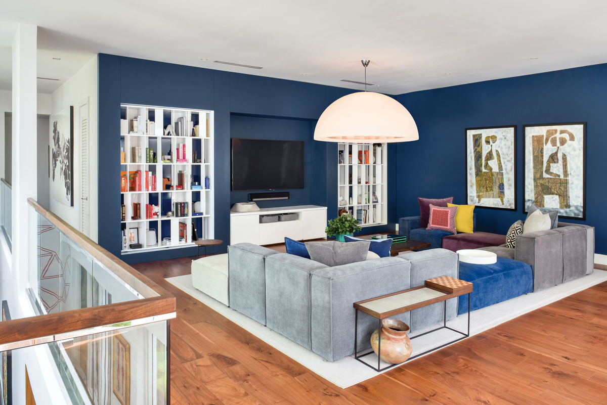 In the family room, the far right doorway was covered to add built in bookcases, while the white cabinet hides refrigerated drawers. The comfortable, modular Romano sofa is upholstered in durable yet tactile velvet.