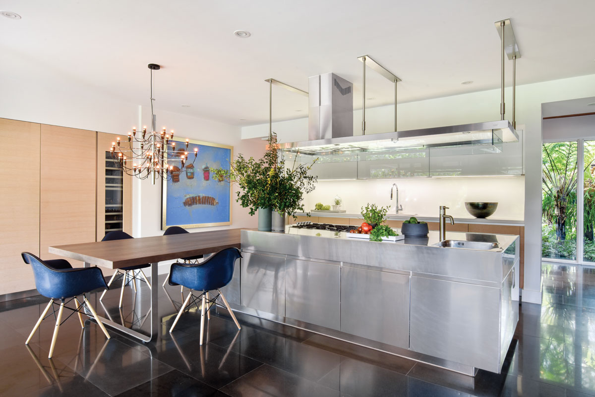Innovative Surfaces of Coral Gables found the scarce lava rock tiles needed to replace damaged ones in the original floor. Counters were swapped out with bright white quartz in the kitchen. The custom wood table is surrounded by blue Eames for Herman Miller chairs.