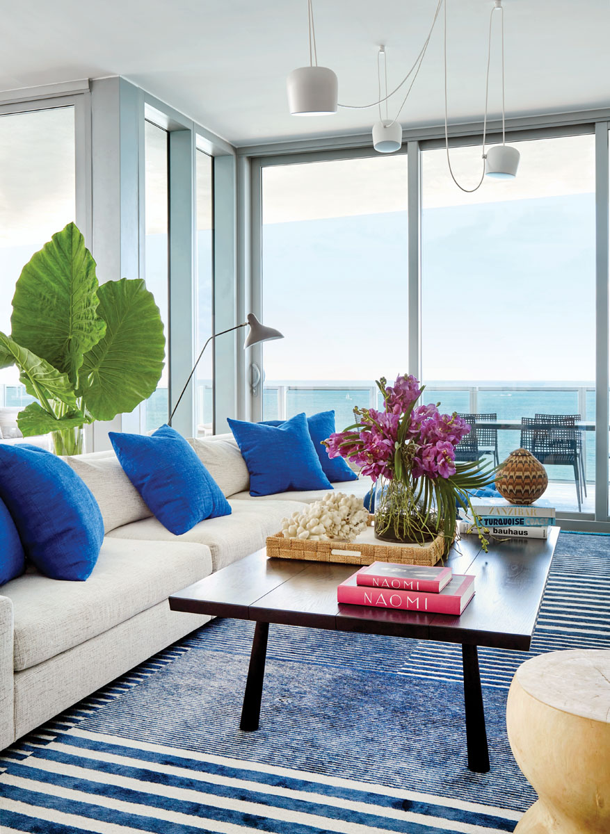 A custom navy rug from Crosby Street Studios and royal blue pillows from Alt for Living accentuate the bright ocean vista. The solid oak coffee table from Black Creek Mercantile & Trading Co. in Brooklyn fuses modernism with the handcrafted feel that Amie Weitzman adores.